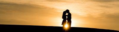 couple qui s'embrasse devant un couché de soleil